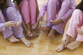 Lower section of four girls painting their toenails — Stock Photo