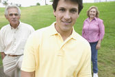 Grown son posing with parents in a park — Stock Photo
