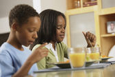 African brother and sister eating breakfast — Stock Photo