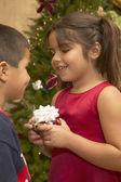 Young Hispanic girl giving brother Christmas gift — Stock Photo