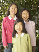 Three young Asian sisters smiling outdoors — Stock Photo