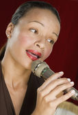 Woman singing into microphone — Stock Photo