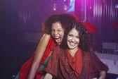 Hispanic women laughing at nightclub — Stock Photo