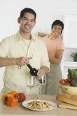 Hispanic man opening wine bottle — Stock Photo