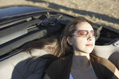 Young woman sleeping in a convertible — 图库照片