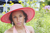 Young woman posing for the camera in a straw hat — Stock Photo