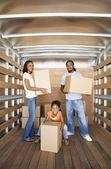 African family holding boxes in moving truck — Stock Photo