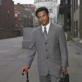 Indian businessman with umbrella in urban area — Stock Photo