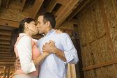 Hispanic couple kissing at construction site — Stock Photo