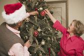 Senior couple decorating a Christmas tree — Stock Photo