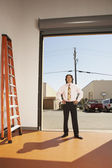 Businessman standing in a garage — Stock Photo