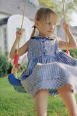 Young girl on swing in yard — Stock Photo