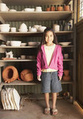 Hispanic girl in pottery shed — Stock Photo