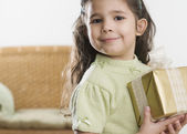 Young Hispanic girl holding gift — Stock Photo