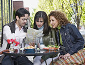 Hispanic friends looking at street map — Stock Photo