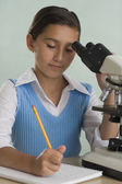 Hispanic girl with microscope and notebook — Stock Photo