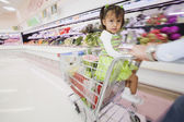 Hispanic girl in shopping cart — Stock Photo
