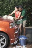 Hispanic couple washing car in driveway — Stock Photo