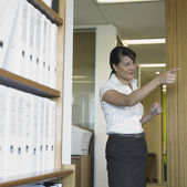 Middle-aged Asian businesswoman pointing — Stock Photo