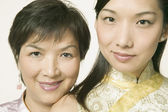 Young Asian woman and her mother in traditional clothes posing for the camera — Stock Photo