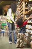 African American mother and young son at health food store — Stock Photo
