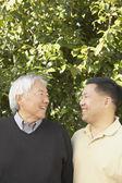 Ledande asiatiska far med vuxen son — Stockfoto