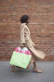 ショッピング バッグで歩く女性の側面図 — ストック写真