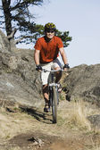 Male cyclist in rugged terrain — Stock Photo