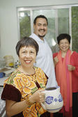 Middle aged woman holding a pitcher in her kitchen — Stock Photo