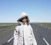 Woman wearing winter jacket standing in middle of deserted road — Stock Photo