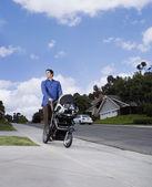 Hispanic man pushing baby stroller — Stock Photo