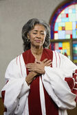African American female Reverend with hands on heart — Zdjęcie stockowe