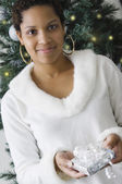 African woman holding gift in front of Christmas tree — Stock Photo