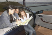 Friends in convertible looking at map — Stock Photo