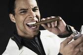 Mixed Race man lighting cigar — Stock Photo