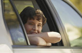 Boy smiling and leaning out of car window — Stock Photo