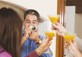 Middle-aged Hispanic man taking photograph of friends — Stock Photo