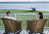 Couple sitting on deck with airplane in yard — Stock Photo