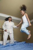 African mother and daughter jumping on bed — Stock Photo