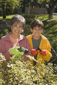 Grandmother and grandson watering plants — Stock Photo