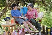 Hispanic grandmother and grandson reading outdoors — Stock Photo