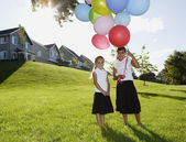 Portrait of two girls holding balloons in backyard — Stock Photo
