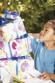 Boy with stack of birthday gifts — Stok fotoğraf