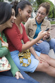 Three girlfriends with mobile phone — Stock Photo