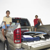 Portrait of siblings in back of truck — Stock Photo