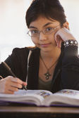 Close up of young Hispanic girl with school book — Stock Photo