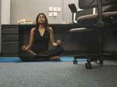 Young woman practicing yoga in office — Stock Photo