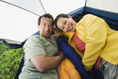 Portrait of couple laying in tent — Stock Photo