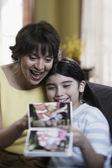 испаноязычное мать и дочь, глядя на фото альбом — Стоковое фото