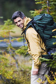 Man smiling while wearing a backpack — Stock Photo